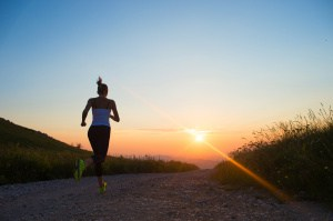 woman running on a mountain road at summer sunset